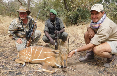 Slater (far left) and Dyason with a trophy harnessed bushbuck taken in Pama Centre Nord.